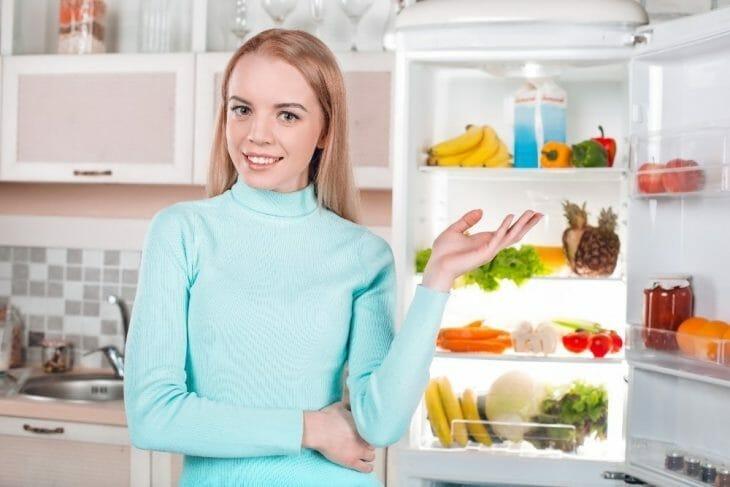 Девушка показывает чистый холодильник