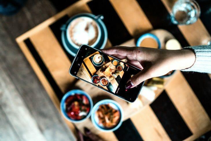 Женщина фотографирует еду