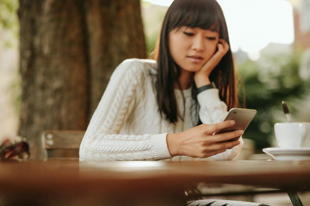 Азиатка за столом с телефоном в руках