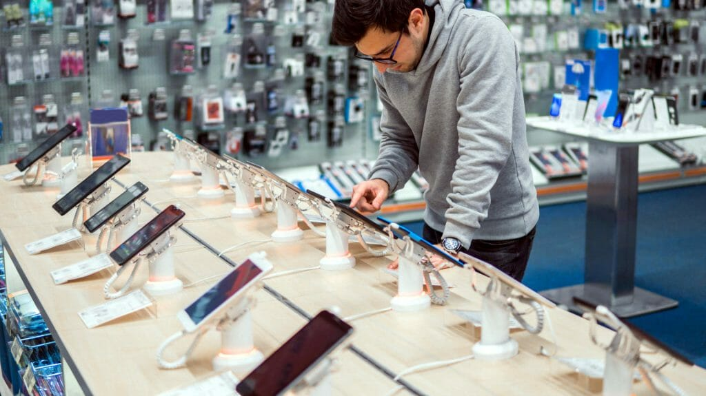 Мужчина возле стенда со смартфонами в магазине электроники