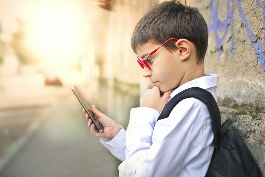 Ребенок в очках держит в руках смартфон