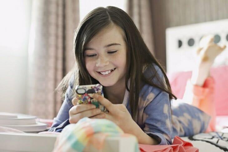 Девочка смотрит на экран смартфона