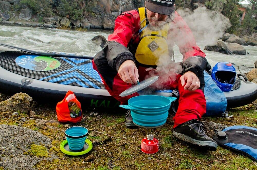 Мужчина готовит еду в походе
