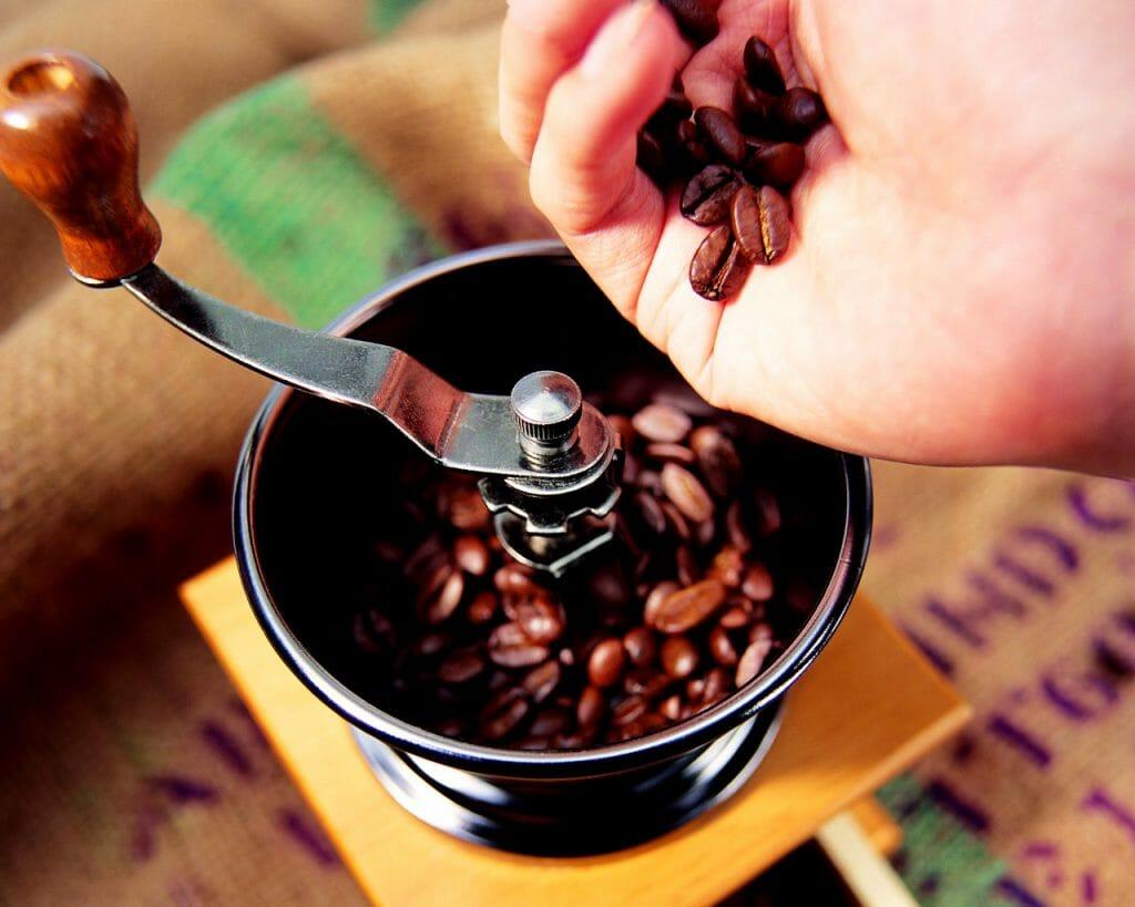 Кофейные зерна засыпают в ручную кофемолку