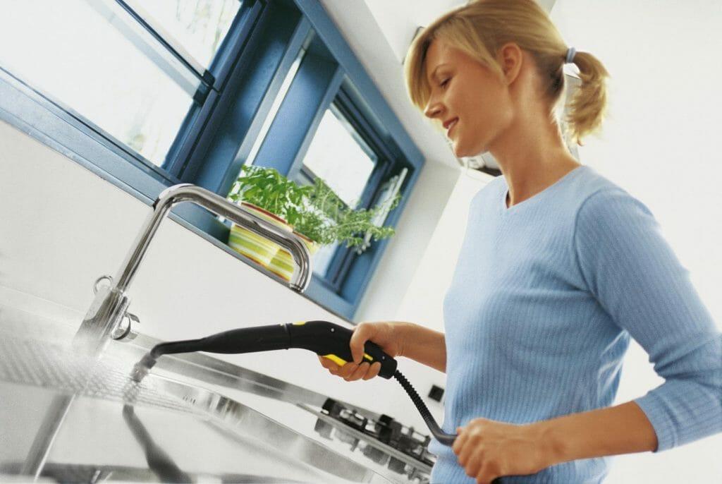 Женщина использует пароочиститель на кухне