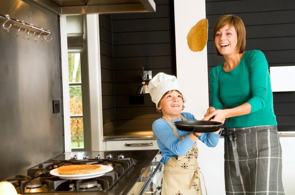 Мама вместе с сыном готовит блины