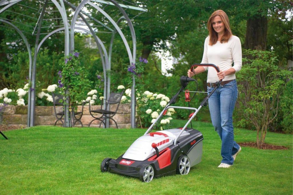 Женщина использует электрическую газонокосилку