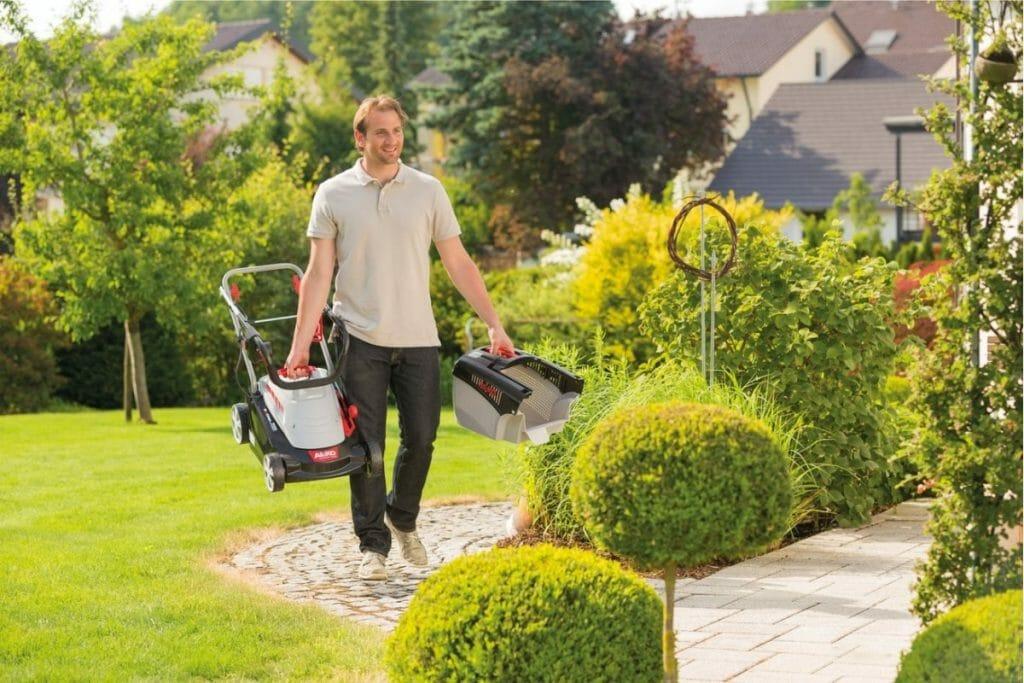 Мужчина несет газонокосилку и травосборник