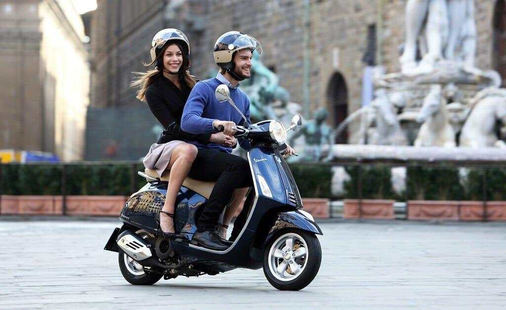 Мужчина и женщина катаются на скутере