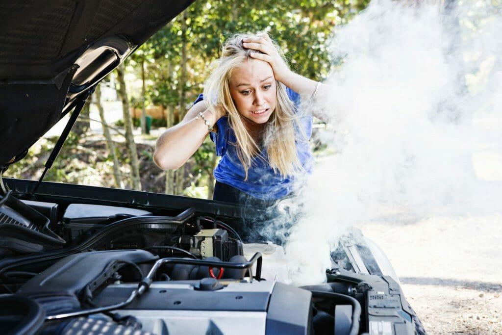 Женщина возле закипевшого радиатора автомобиля