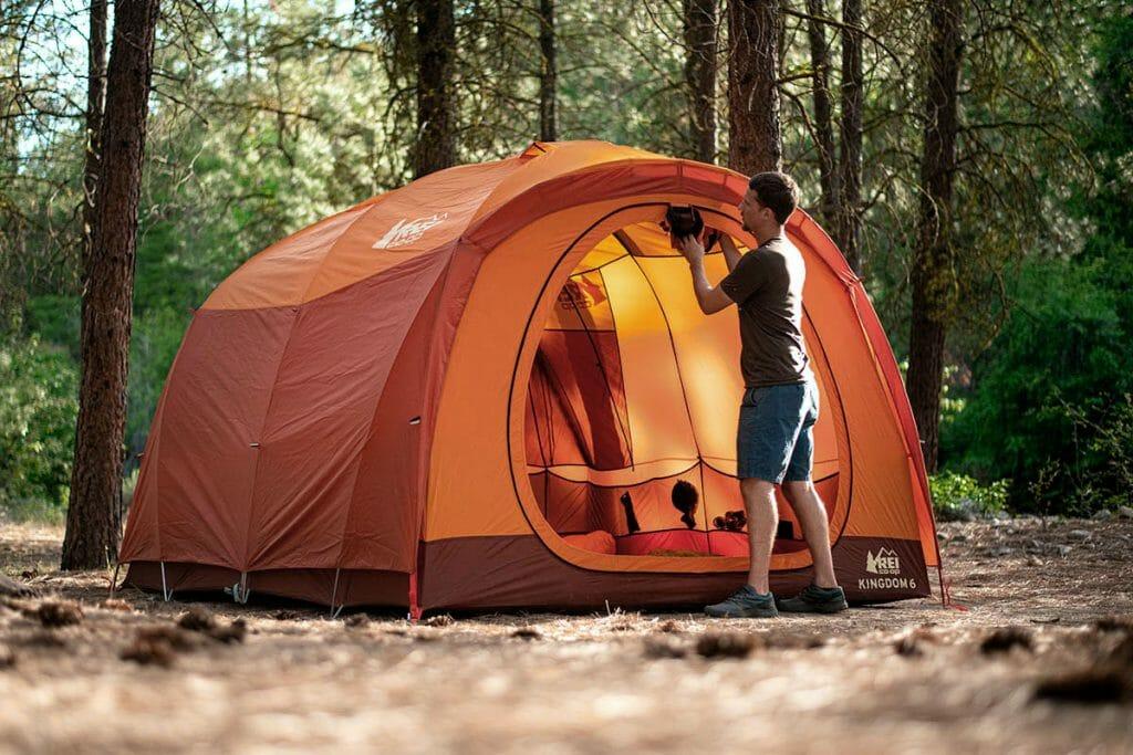 Мужчина устанавливает двухслойную палатку