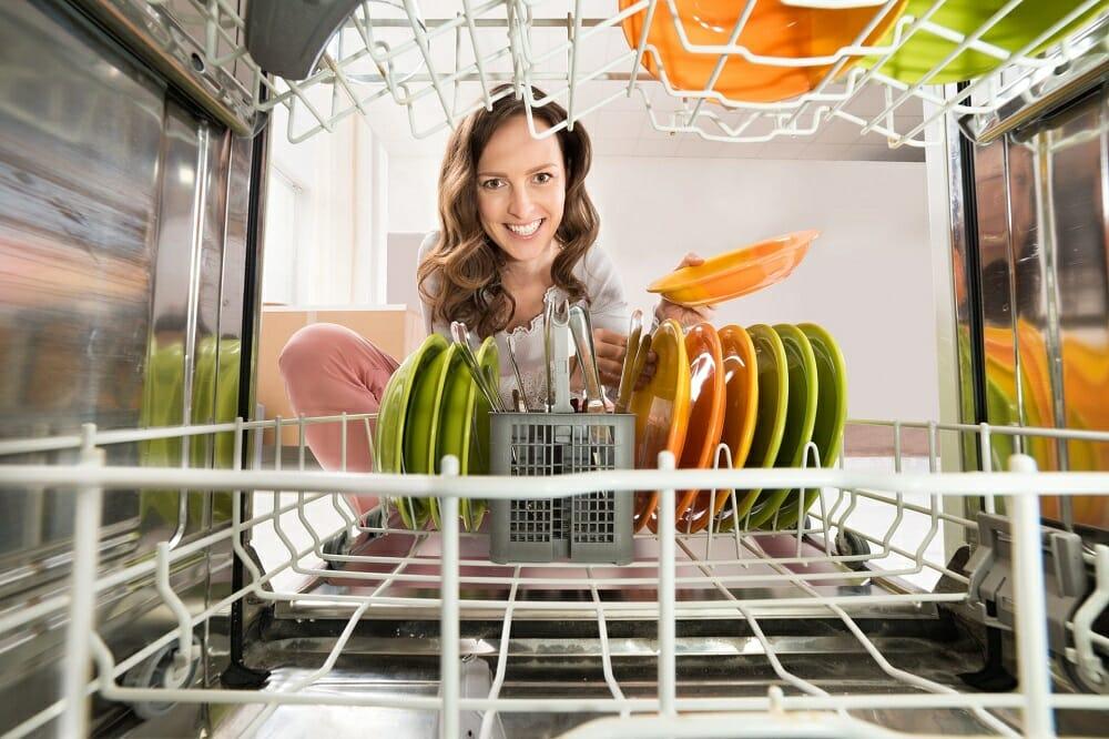 Девушка размещает посуду в посудомойку