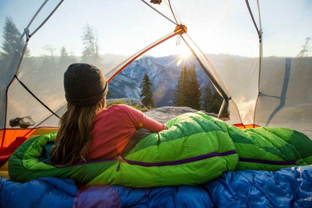 Туристка в палатке смотрит на солнце