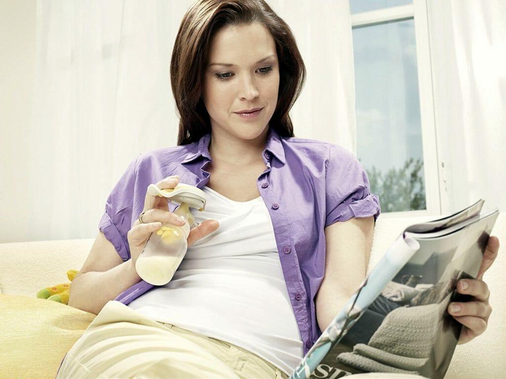 Женщина сцеживает молоко молокоотсосом