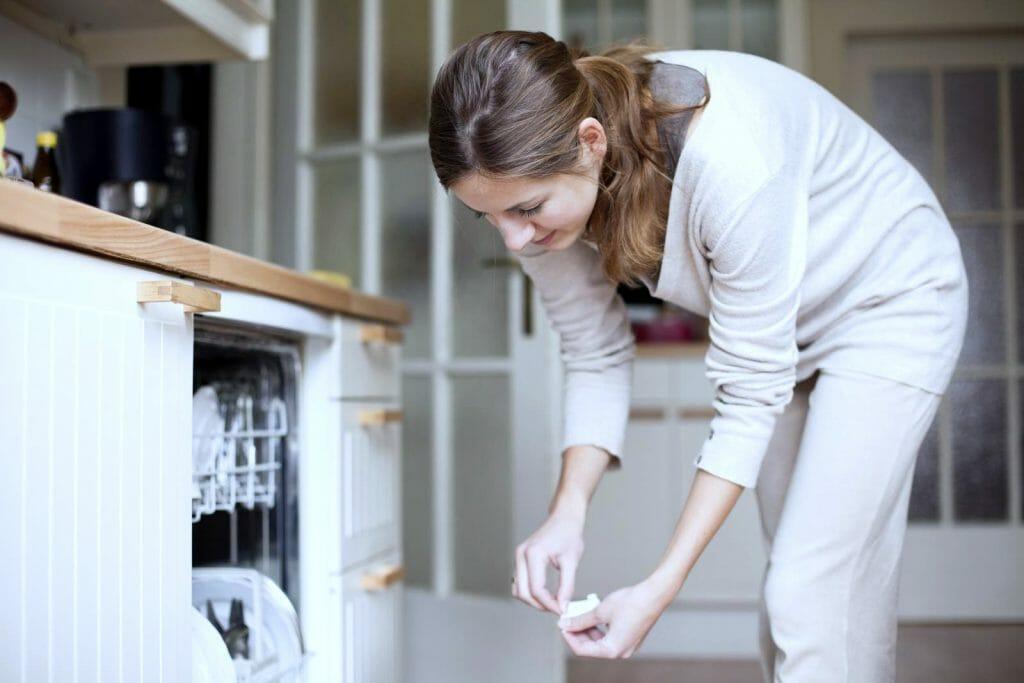 Женщина загружает посудомойку