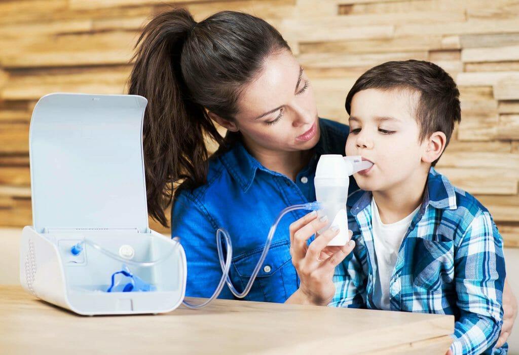 Мальчик возле мамы пользуется небулайзером
