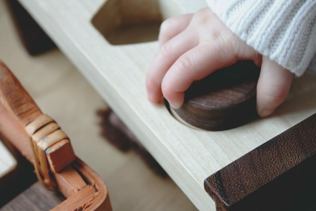 Младенец играет с деревянными игрушками