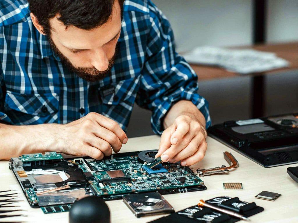 Мужчина достает процессор из ноутбука