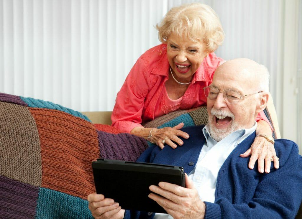 Пенсионеры смеются с планшета
