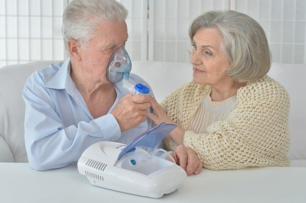 Пожилой мужчина использует компрессорный небулайзер
