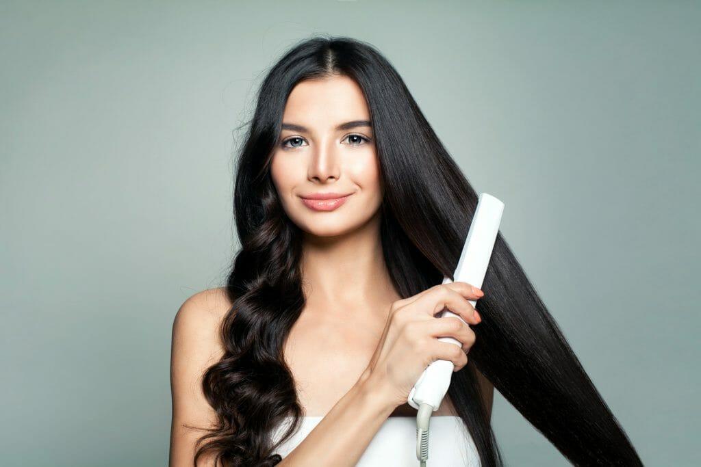 Женщина использует выпрямитель для волос