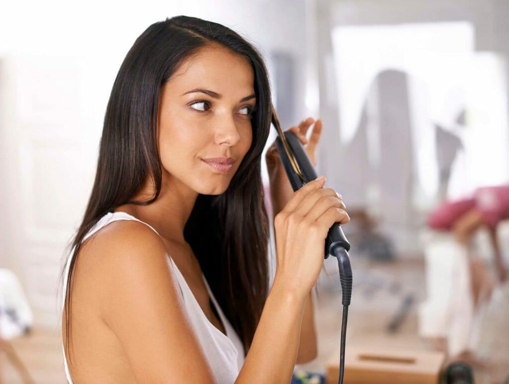 Женщина выпрямляет волосы